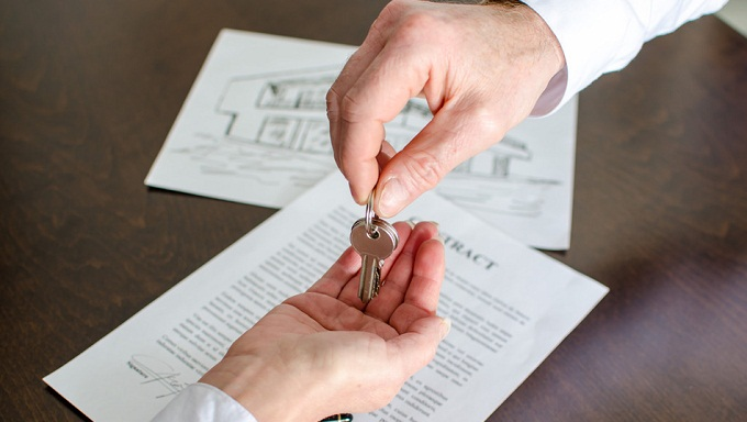 Estate agent giving house keys to customer
